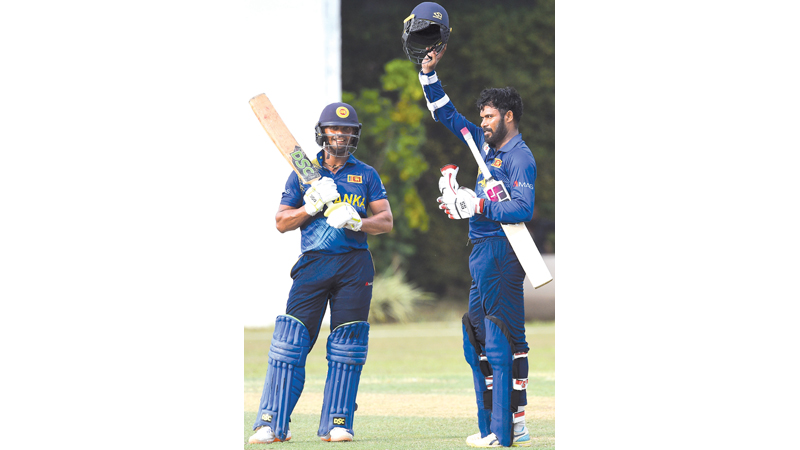 Sri Lanka Cricket XI  captain Upul Tharanga celebrates his century watched by partner Asela Gunaratne who helped him in a stand of 198.
