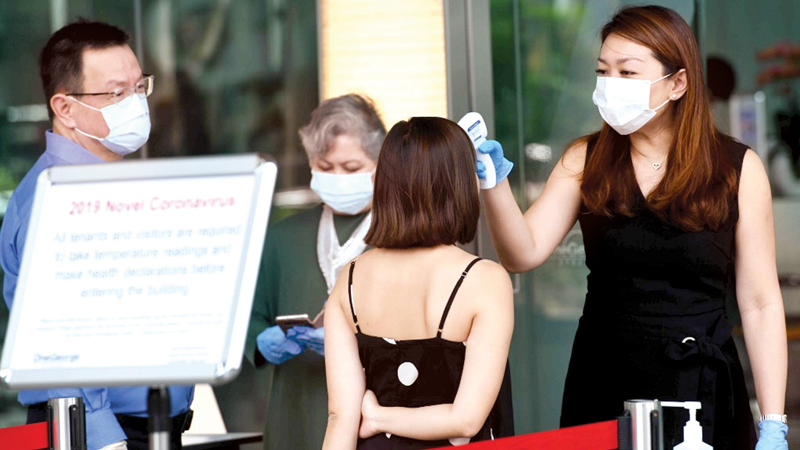 Building management staff conduct temperature screenings of visitors and tenants of a building in the financial district of Singapore on Saturday in the wake of the spread of the COVID-19.