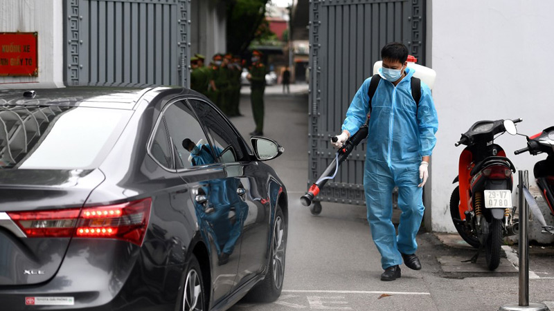 A health worker disinfects a street in Hanoi, Vietnam (AFP)