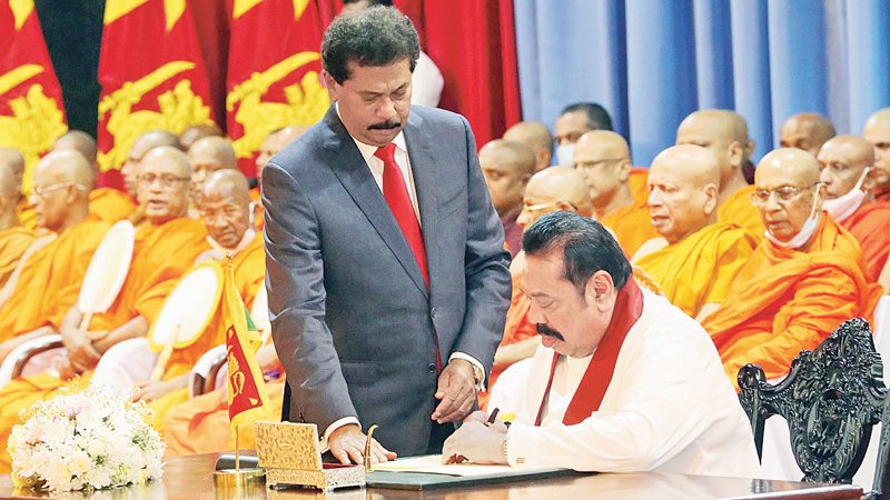 Prime Minister Mahinda Rajapaksa assumed duties at Temple Trees amidst the chanting of Seth Pirith by the Maha Sangha yesterday morning.The Prime Minister placing his signature on a document while the Prime Minister's Secretary Gamini Senerath looks on. Picture by Wimal Karunatilleke.