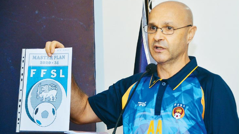 Amir Alagic, the national football caoch displays the future development  guide book designed for FFSL