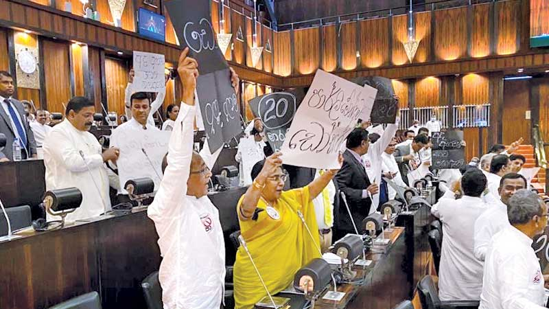 Opposition MPs carrying slogans protesting the Twentieth Amendment Bill in Parliament yesterday.Picture by Wimal Karunatilake.
