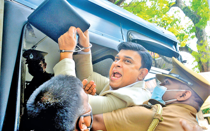 SJB MP Ranjan Ramanayake gesturing to the media before being taken away to the Pallansena quarantine centre after his conviction yesterday. Picture by Thushara Fernando