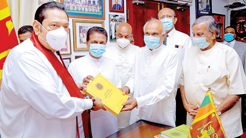 All Ceylon Buddhist Congress (ACBC) president Jagath Sumathipala handing over the report of the Buddhist Rights Commission to Prime Minister Mahinda Rajapaksa yesterday. Picture courtesy Prime Minister's Media Division