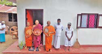 The brother and sister with the monks in front of the  newly-constructed house.