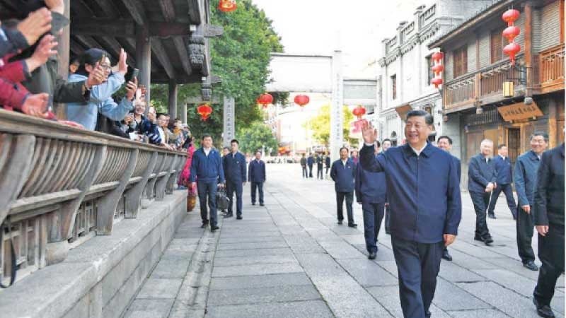 Chinese President Xi Jinping who is also General Secretary of the Communist Party of China Central Committee and Chairman of the Central Military Commission greets people while visiting the historical and cultural block of Sanfangqixiang (Three Lanes and Seven Alleys) in Fuzhou, Fujian Province on March 24, 2021. - XINHUA