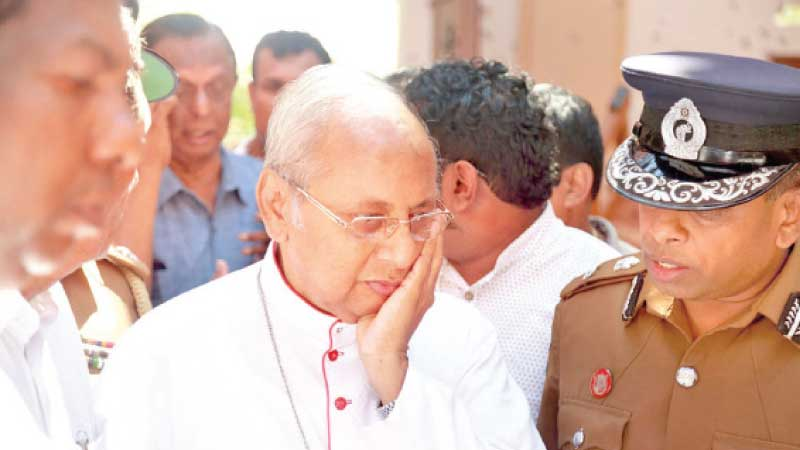 Cardinal Malcolm Ranjith reacts as he visited the site of one of the bomb blasts.