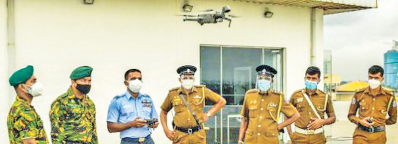 An Air Force officer flying a drone, while STF and police personnel look on.  Picture courtesy: Air Force Media Unit.