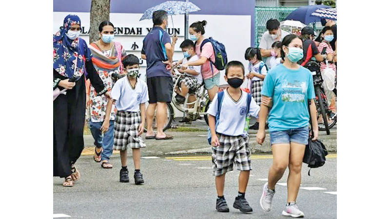 People wearing face masks cross a road amid the COVID-19 outbreak in Singapore.