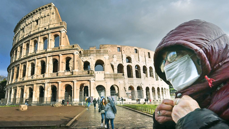 A man in face mask stands near The Colosseum in Rome.