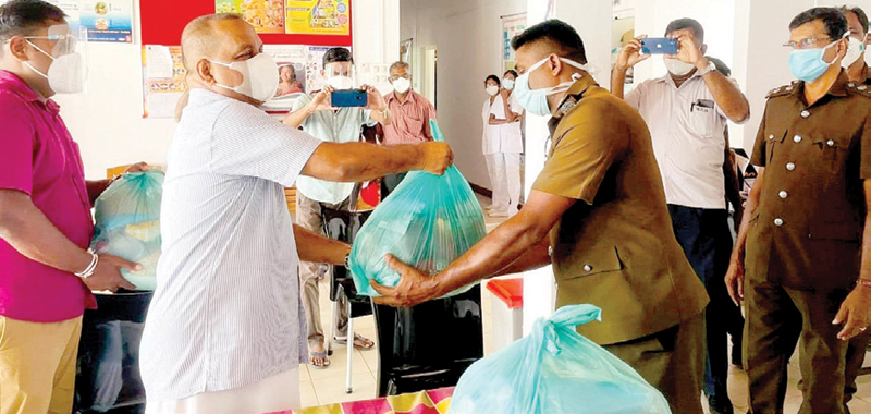 Minister Mahinda Amaraweera handing a pack of essential items to a health official.