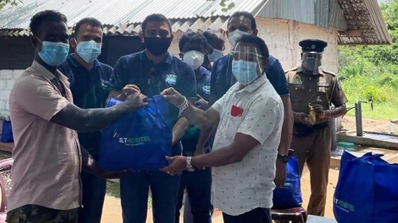 Trincomalee Government Agent Saman Darshana Pandikorala hands dry rations packs to families in the Trincomalee area accompanied by SLT-MOBITEL Officials