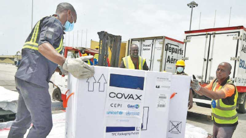 Workers unload a shipment of AstraZeneca COVID-19 vaccine bearing Covax stickers from a plane.