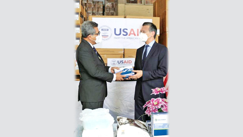 U.S. Embassy Charge d'Affaires Martin Kelly making a symbolic presentation to Secretary to the Ministry of Health Dr. S.H. Munasinghe.