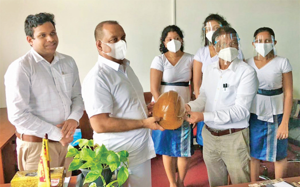 Environment Minister Mahinda Amaraweera was being introduced to an Eco-friendly fiber helmet by Coir Creations Managing Director C.S. Gamage.