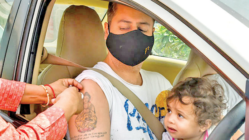 A health worker administers a dose of COVID-19 vaccine to a beneficiary at a drive-through vaccination camp, at Saket in New Delhi. - PTI