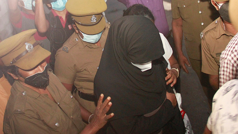 Police officers escorting MP Bathiudeen's wife after she was remanded