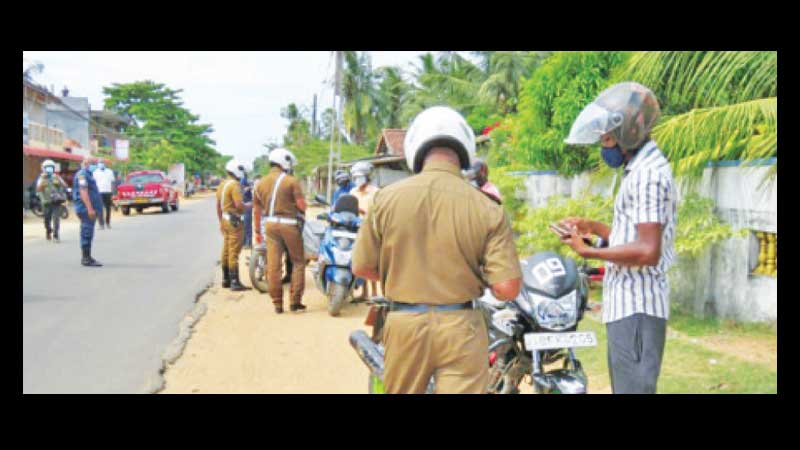 A group of Police Officers checking motorcyclists at a checkpoint in Batticaloa.