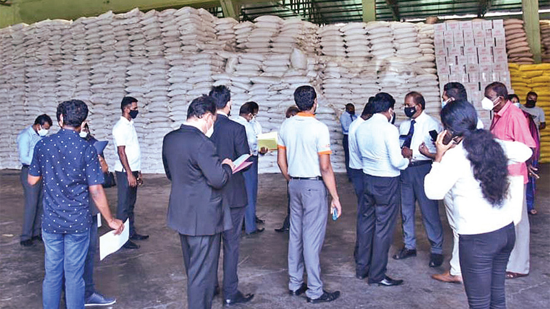 Consumer Affairs Authority officials inspecting sugar stocks hoarded by traders in Kandy yesterday. Picture by Chinthaka Kumarasinghe