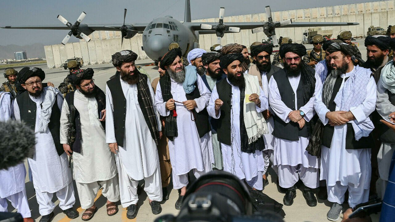 Taliban leaders pose before a USAF C-130 left behind at the Kabul Airport