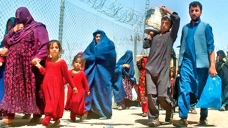 Afghan refugees walk through a security barrier as they enter Pakistan through a common border crossing point in Chaman, Pakistan on Sunday.