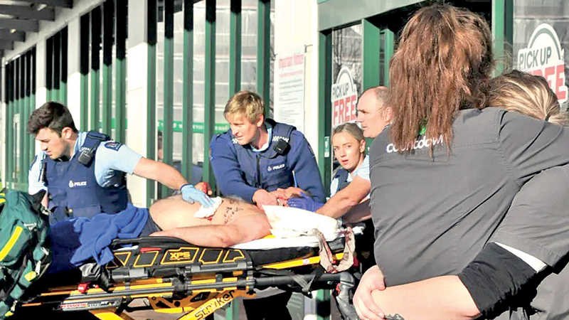 A victim of the supermarket stabbing in New Zealand is taken to hospital as shocked staff members try to console each other.
