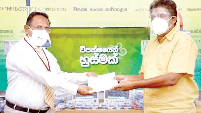 Opposition Leader Sajith Premadasa handing over the medical equipment to the MOH of Kurinchakerny area Dr. A.M. Ajith.