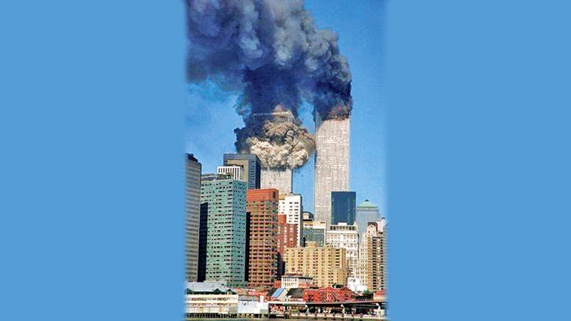 The south tower begins to collapse as smoke billows from both towers of the World Trade Center, in New York, on September 11, 2001.