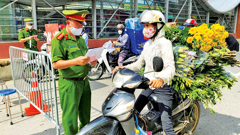 Vietnamese Police officers inspect authorised travel documents of commuters at a check point during the first day of the extended lockdown in Hanoi, Vietnam on Monday.