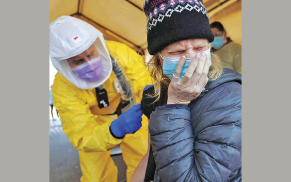Lori Tonge grimaces as she gets a flu shot in Salt Lake City, Utah State. Volunteers with the Rescue Mission of Salt Lake provided vaccines for people.