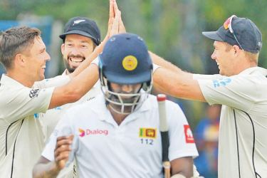 New Zealand fast bowler Trent Boult (L) celebrates with team mates William Somerville (centre) and Tim Southee his 50th Test wicket with the dismissal of Sri Lanka's Angelo Mathews on the second day of the second cricket Test at the P Sara Oval on Thursday. – AFP