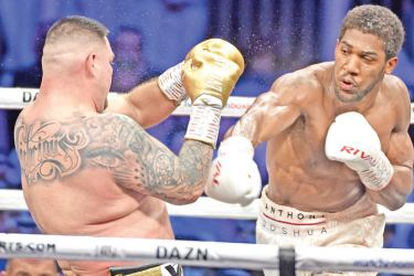 British boxer Anthony Joshua (white trunks) competes with Mexican-American boxer Andy Ruiz Jr (golden trunks) during the heavyweight boxing match for the IBF, WBA, WBO and IBO titles in Diriya, near the Saudi capital on Saturday. Joshua reclaimed his world heavyweight crown from Andy Ruiz, outclassing the Mexican-American to score a unanimous points victory. – AFP