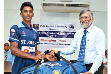 SLC Tournament Committee Chairman Bandula Dissanayake handing over cricket gear to St John's college player.