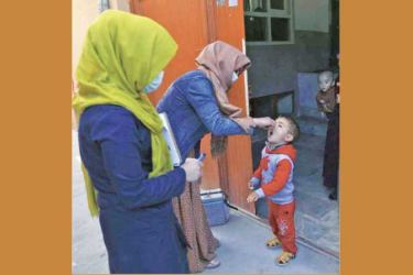 Health workers administer a polio vaccine to a child during a polio vaccination campaign in the city of Kabul, Afghanistan on Tuesday.