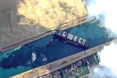 Tug boats and dredgers attempt to free the MV Ever Given from the Suez Canal in this satellite image taken Friday, March 26. (AFP)