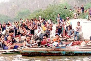 Refugees flee Myanmar for Thailand after airstrikes.