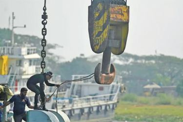 Rescuers try to recover a capsized boat in Shitalakshya River, in Bangladesh