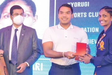 The Minister of Sports and Youth Affairs Namal Rajapaksa handing over the plaque to silver medalist in women's 49 kg weight category of the 13th South Asian Games. Pushpa Kumari at the felicitation ceremony. The President of Sri Lanka Taekwondo Federation Kanchana Jayaratne is also in the picture.