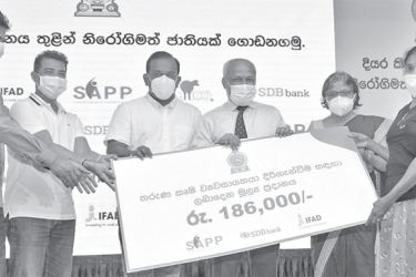 Presenting of a loan facility to an entrepreneur from the SDB bank by Mahindananda Aluthgamage  and other  guests.