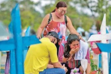 People visit the Nossa Senhora Aparecida cemetery in Manaus, Brazil to mourn the loss of their loved ones who died of COVID-19.