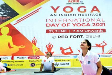 Practitioners perform a yoga position during an event to mark International Yoga Day at the Red Fort in New Delhi. - PTI