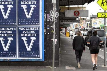 People walk past a sign encouraging people to get vaccinated inMelbourne, Australia as the city experiences it's sixth lockdown as it battles an outbreak of the Delta variant of coronavirus.