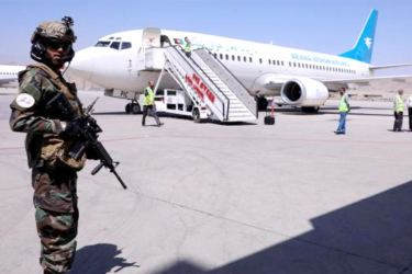 A fighter from the Taliban's Badri 313 special unit stands guard near a Ariana Afghan Airlines plane at Hamid Karzai International Airport in Kabul on Sunday.