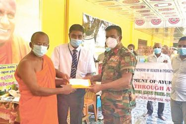 Chief Incumbent of the Deegawapi Parivara Ven. Bothivela Chandrananda Thera receiving the first pack of Ayurvedic medicines from Army Camp 241 Division Commander Colonel A.M.C. Abeyakoon and Nintavur Ayurvedic Research Hospital Acting Director Dr. K.L.M. Nagfer.