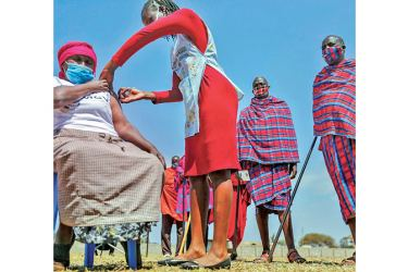 Maasai men queuing to receive the AstraZeneca coronavirus vaccine look over as a woman receives a jab at a clinic in Kimana, southern Kenya on Saturday.