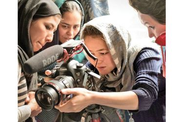 A female Afghan photo journalist and colleagues on the job.
