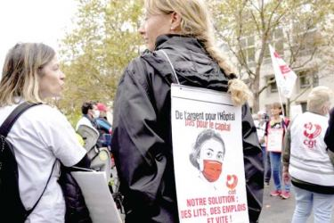 """A medical worker holds a placard reading : """"Money for Hospital, Not for the Capital, Our Solution Hospitals beds, Employs and quick"""", during a protest outside the Health Ministry, in Paris."""