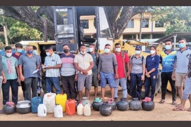 Police Officers along with the seized illicit liquor.