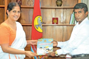 Eastern Province Governor Anuradha Yahampath receiving the first copy of the workbook for pre-school children from Chairman of the Provincial Pre-School Bureau Pradeep Tennakoon.