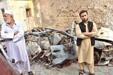 Aimal Ahmadi (R), brother of Ezmarai Ahmadi, who was one of 10 people killed in a US drone strike in Kabul that the US now says was a mistake, stands next to the wreckage of a vehicle destroyed in the attack.